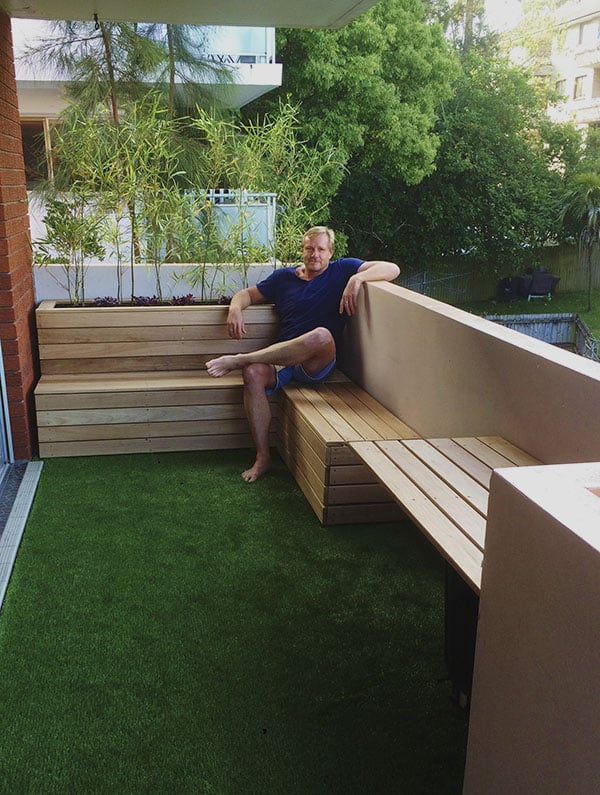 home owner sitting on a timber planter box in Sydney