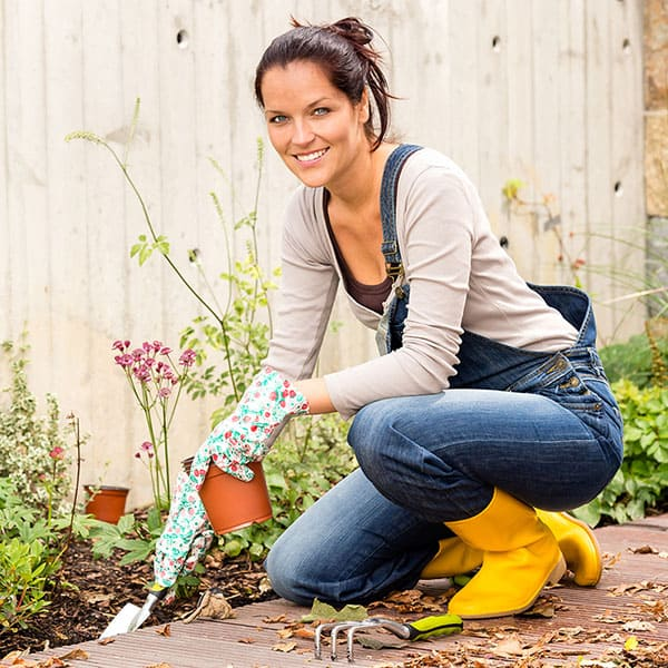 woman getting rid of weeds in the garden