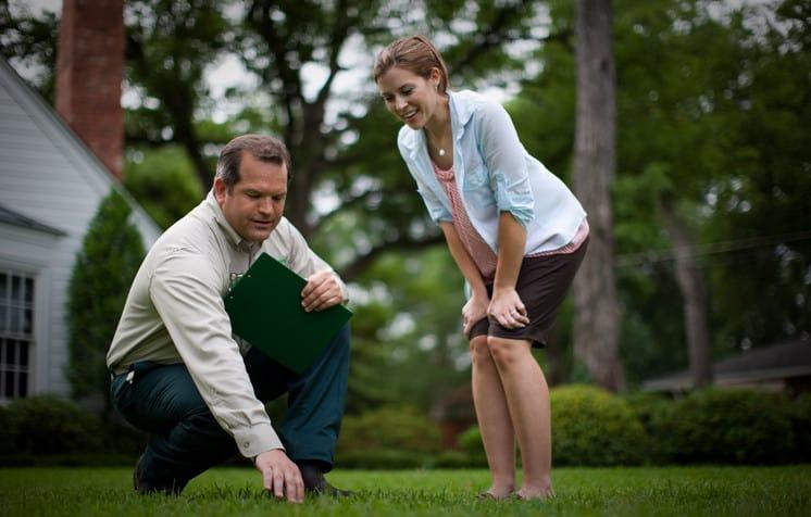 landscape architect explaining lawn aeration to a lady