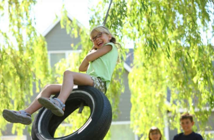 girl playing on a tire swing in the backyard