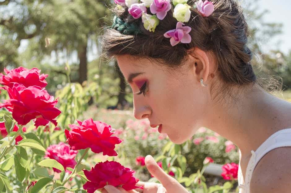 woman inhaling the fragrance of flowers in the garden