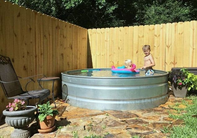 kid playing in a stock tank pool in his backyard
