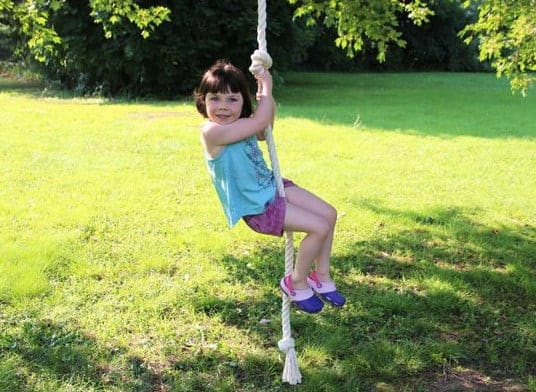 little girl swinging on a rope swing